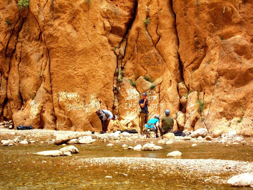 This photo shows rock climbers in Todra Gorge Morocco inbetween the rock face and river.