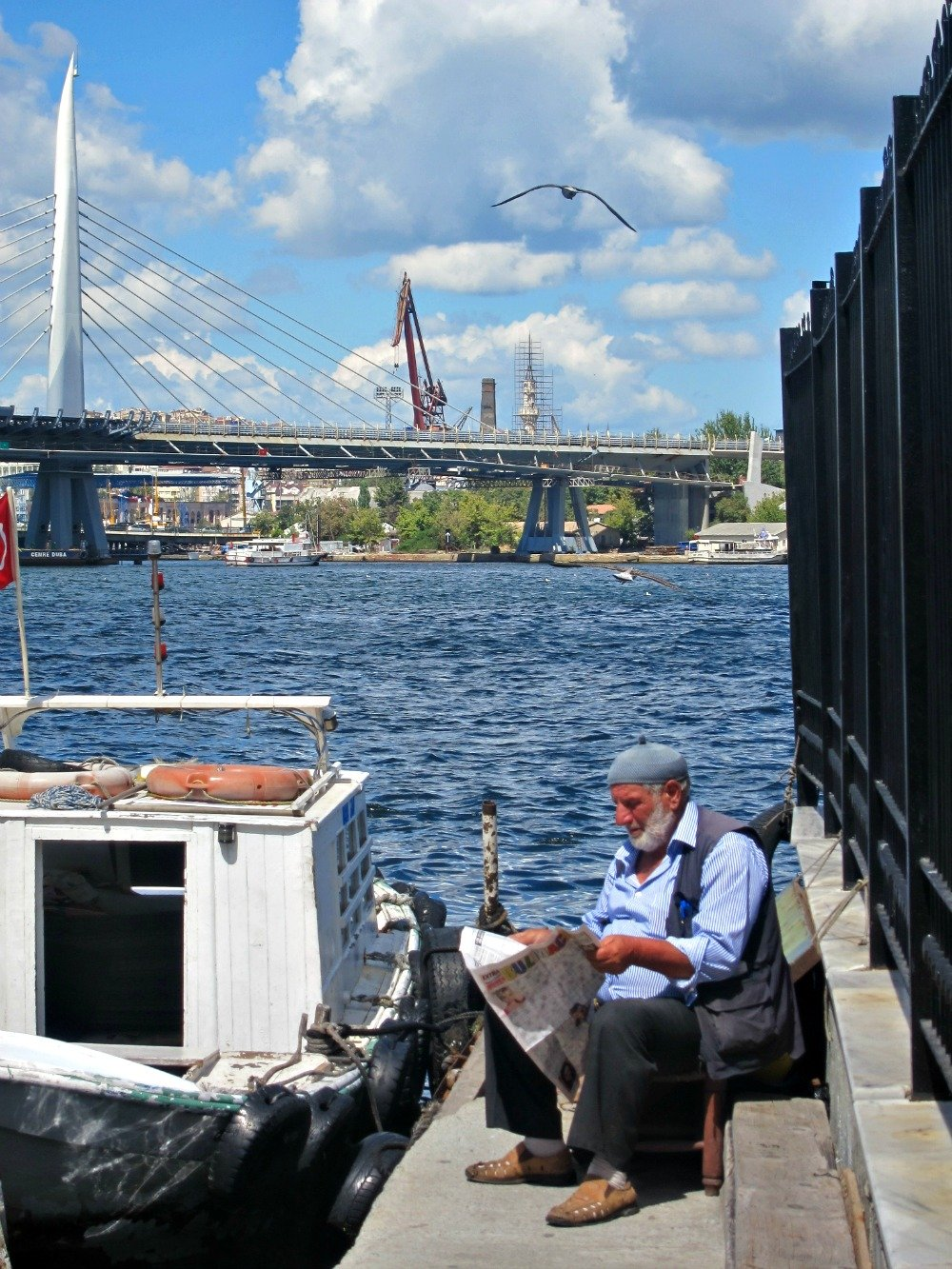 Man sitting beside the Golden Horn reading Istanbul Newspaper