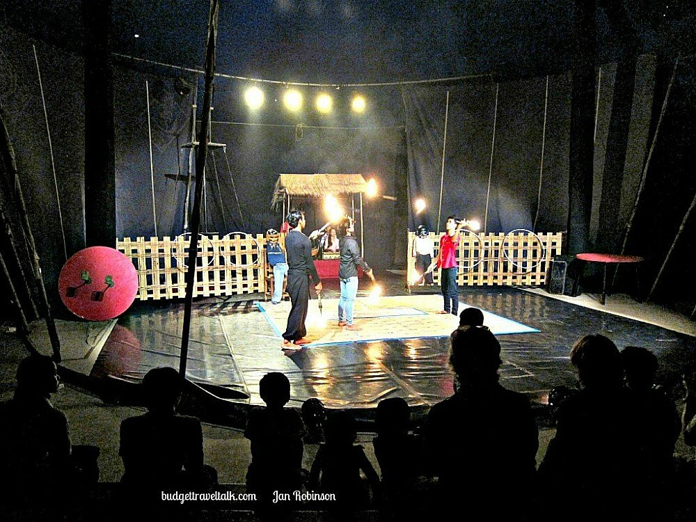 Photo taken in a Circus Tent in Battambang Cambodia with three gymnasts performing with hoops