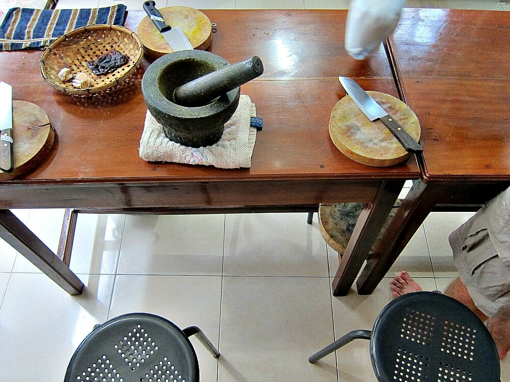 Photo of timber bench with mortar and pestle and round chopping board and knife at cooking school in Battambang