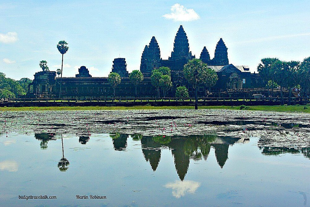 Photo of Angkor Wat with blue sky and Wat and Sky reflected in the still lake at the front. Siem Reap