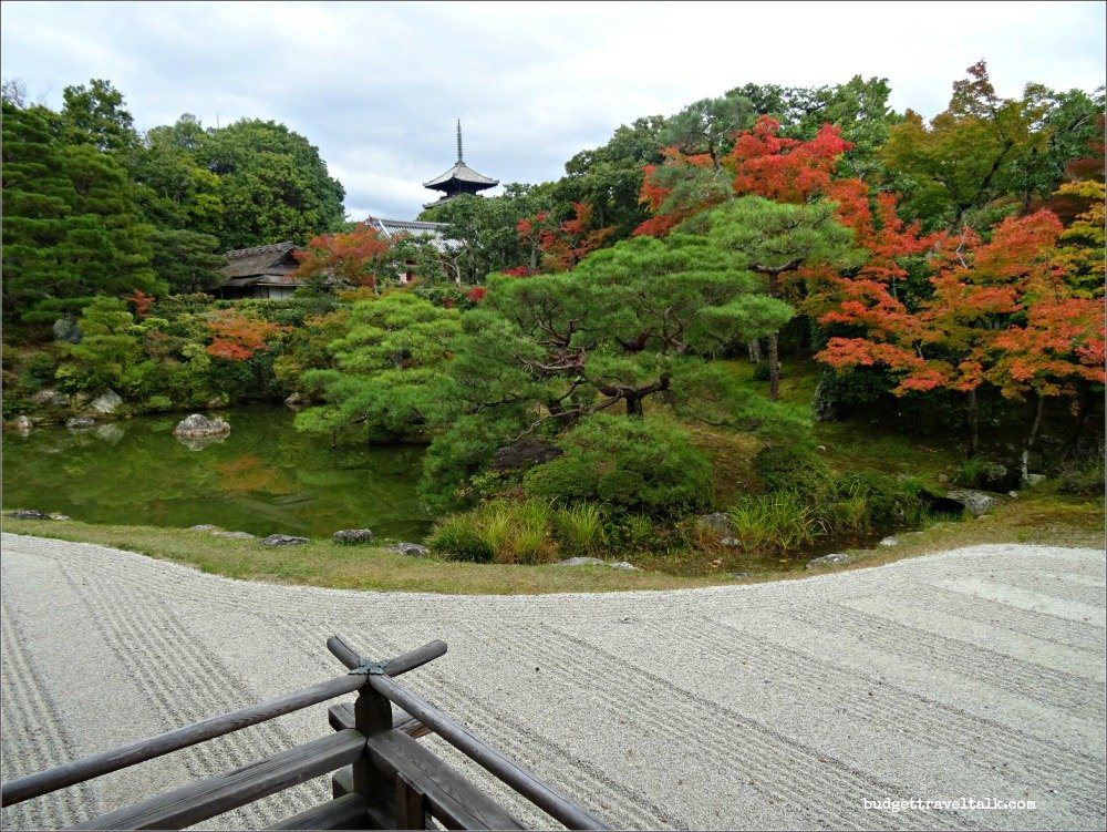 Photo of the raked Garden of Omuro Palace at Ninna-Ji in the foreground with the autumn colours of the gardens behind and the borrowed landscape of the pagoda in the background.