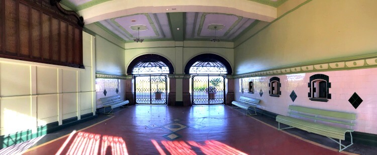 Ticket Office Old Townsville Railway Station with it's red tiled floor and shiny white and green wall tiles, metal gates and War Memorial for Railway Workers