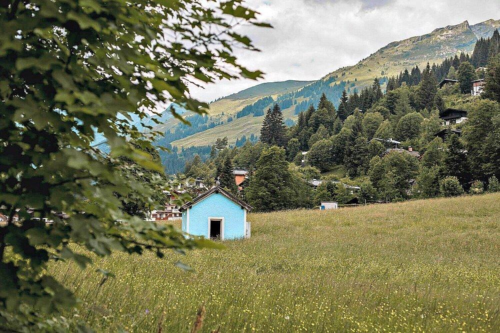 A pretty blue Church in a grassy field in Saalbach Hinterglemm Austria