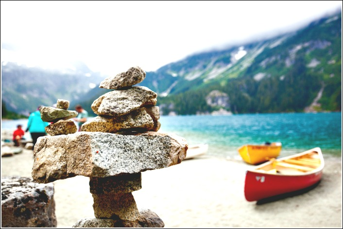 Photo of a rock cairn and canoes beside a blue lake in the Canadian Rockies