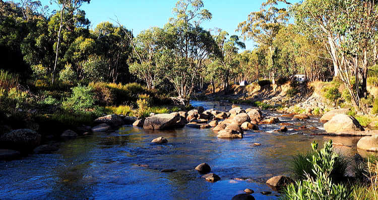 Outback river in Australia with shallow water smooth rocks and gum trees is a great camping spot and you can just see a caravan through the trees