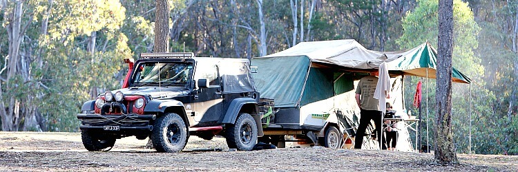 Black Jeep Vehicle towing a camping trailer set in the Australian Bush and used for free camping.
