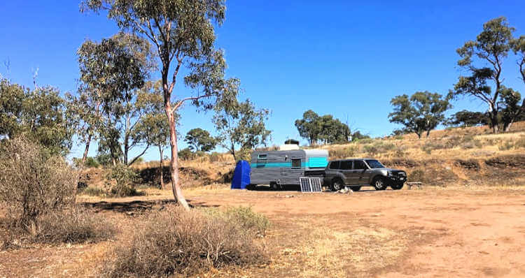 An Old Caravan free camping in the Australian outback. Dry red soil blue sky and gum trees with a caravan painted gun metal grey with bright blue trim.