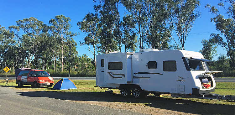 Large white caravan with slide out is set up in a free roadside camp in Australia. Beside it is a small 2 man blue tent and a orange campervan. All set up on green grass between a service road and the Bruce Highway