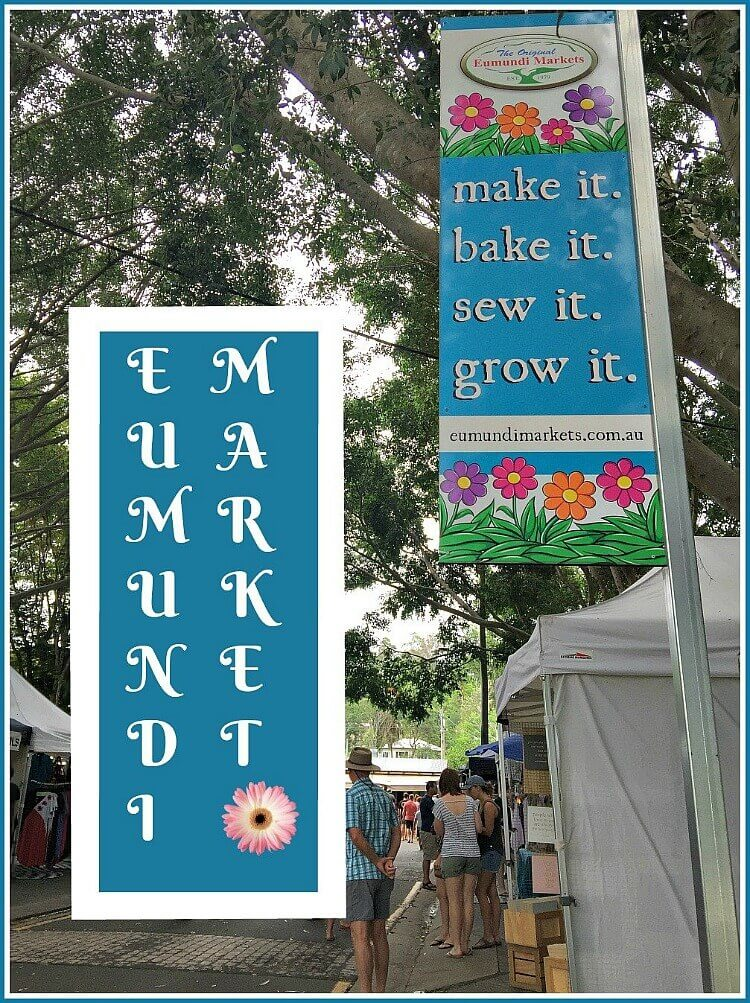 The Original Eumundi Market sign with market stalls under the canopy of big trees at Eumundi Markets Sunshine Coast