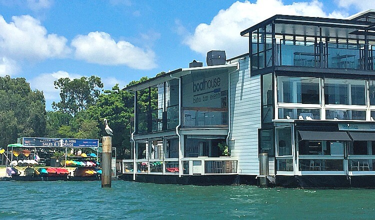 The emerald green Noosa River with the boathouse restaurant and kayaks for hire