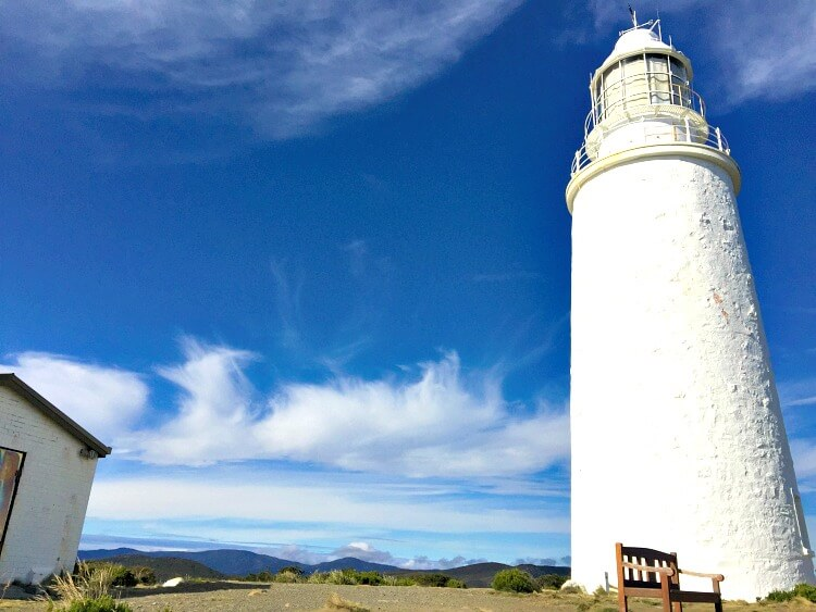 a close view of Bruny Island Lighthouse with blue sky background and bench seat foreground