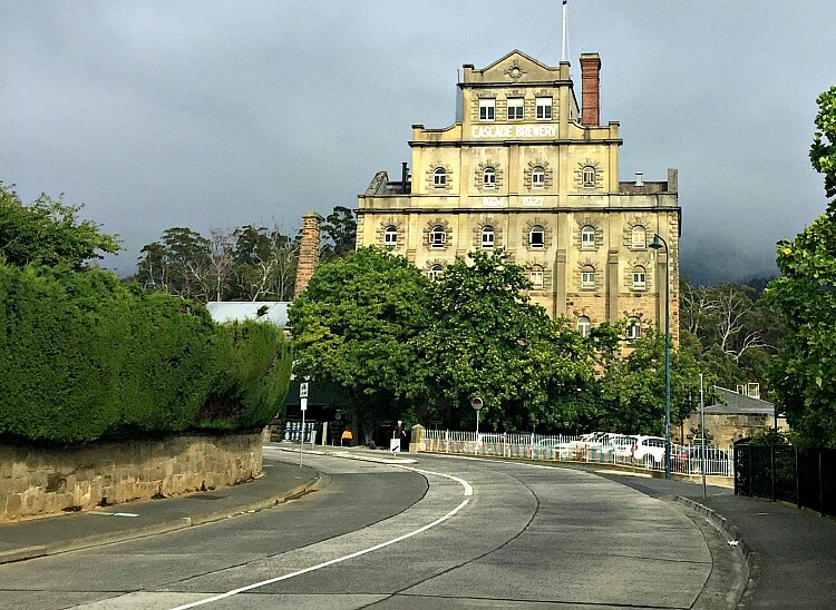 Historic gothic sandstone Cascade Brewery building with green trees and grey road in front and grey skies behind