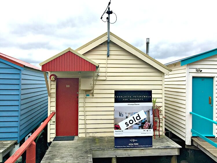 Cream coloured Cornelian Bay Boat House with red door and sold sign