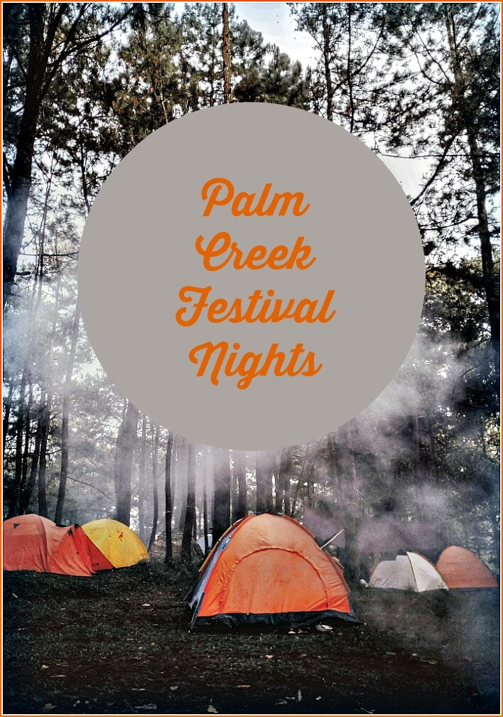 Dark forest and bright orange yellow and white tents Palm Creek Festival
