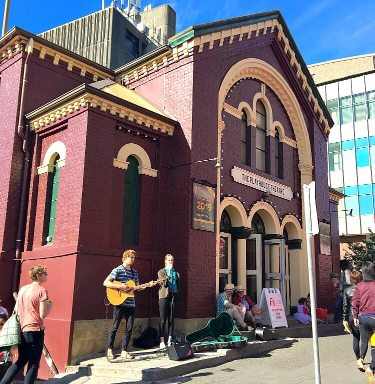 Buskers outside the dark brick Playhouse Theatre on Sunday morning Farm Gate Market Hobart