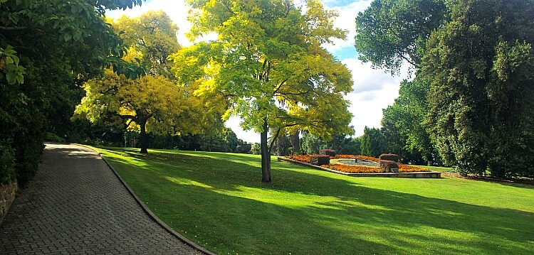 Green sloping lawns, yellow leafed trees and floral clock at Royal