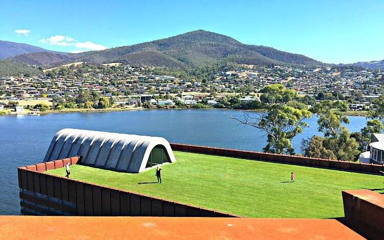 Rust coloured walkway at Mona overlooking green grass and Faros Restaurant and Berriedale Bay Hobart