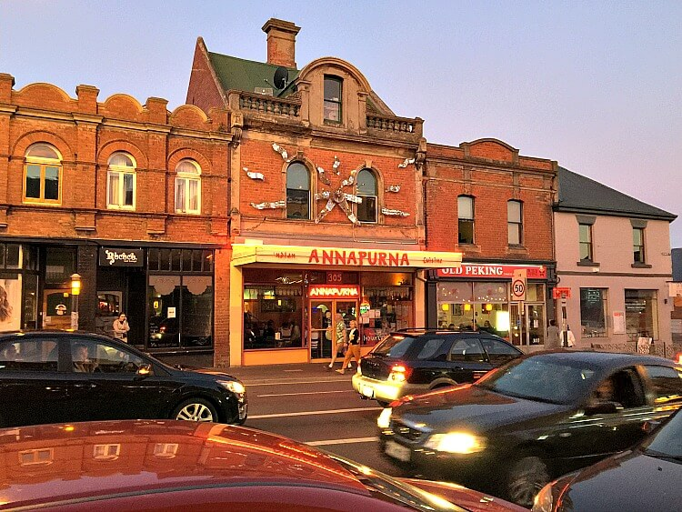 Brown brick buildings glow orange at dusk in Elizabeth Street North Hobart