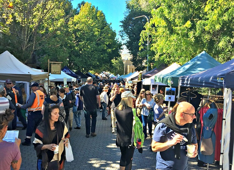 Crowds at Salamanca Market Hobart with blue skies green trees and marquees