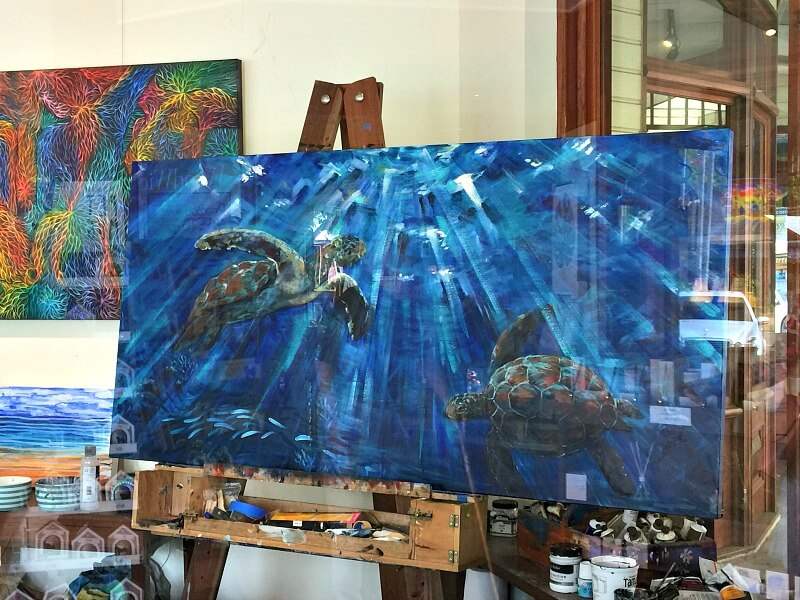 An example of Montville Art with an underwater scene of two turtles in blue sun-streaked water