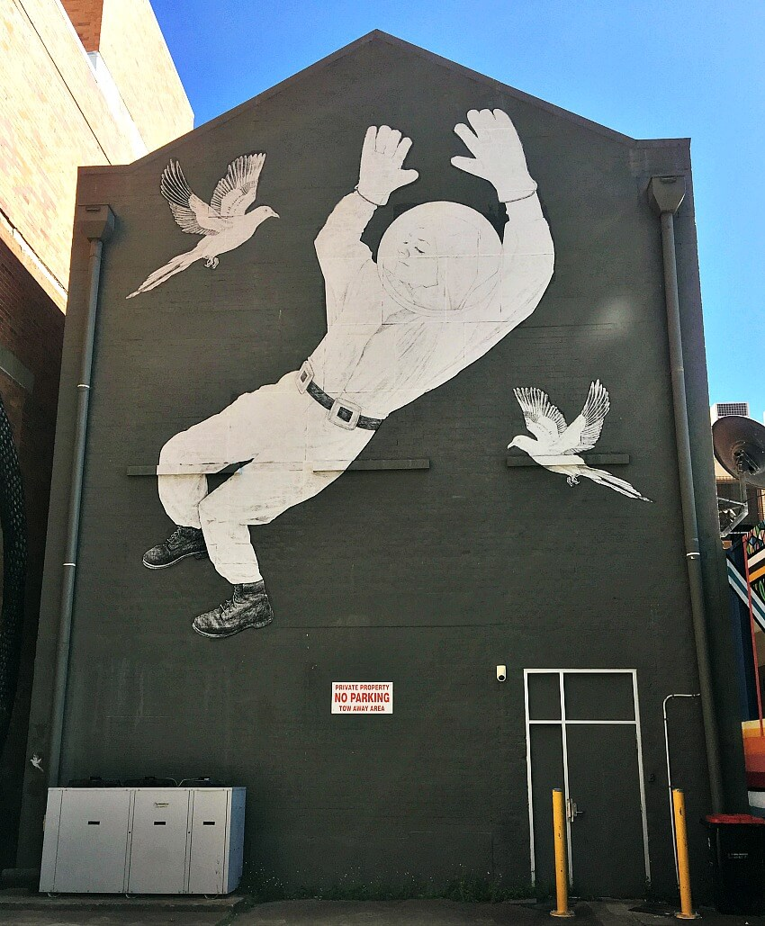 Townsville Street Art Paste Up called Perpetual Motion by Baby Guerilla of a diver floating on a dark grey background
