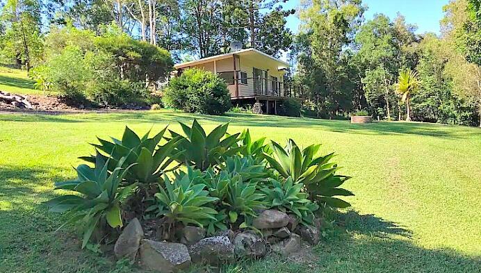 Romantic Getaway Cabin at Doonan in Noosa Hinterland Gardens in front and trees behind house